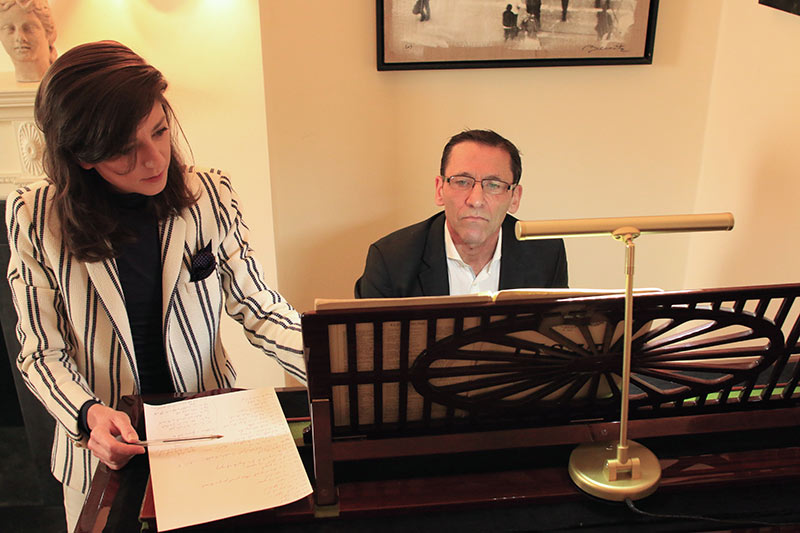 Celine explaining a musical score to Christian at the London Piano Institute