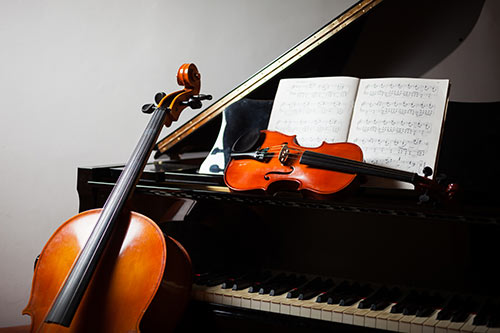 Grand piano with musical score and cello and violin