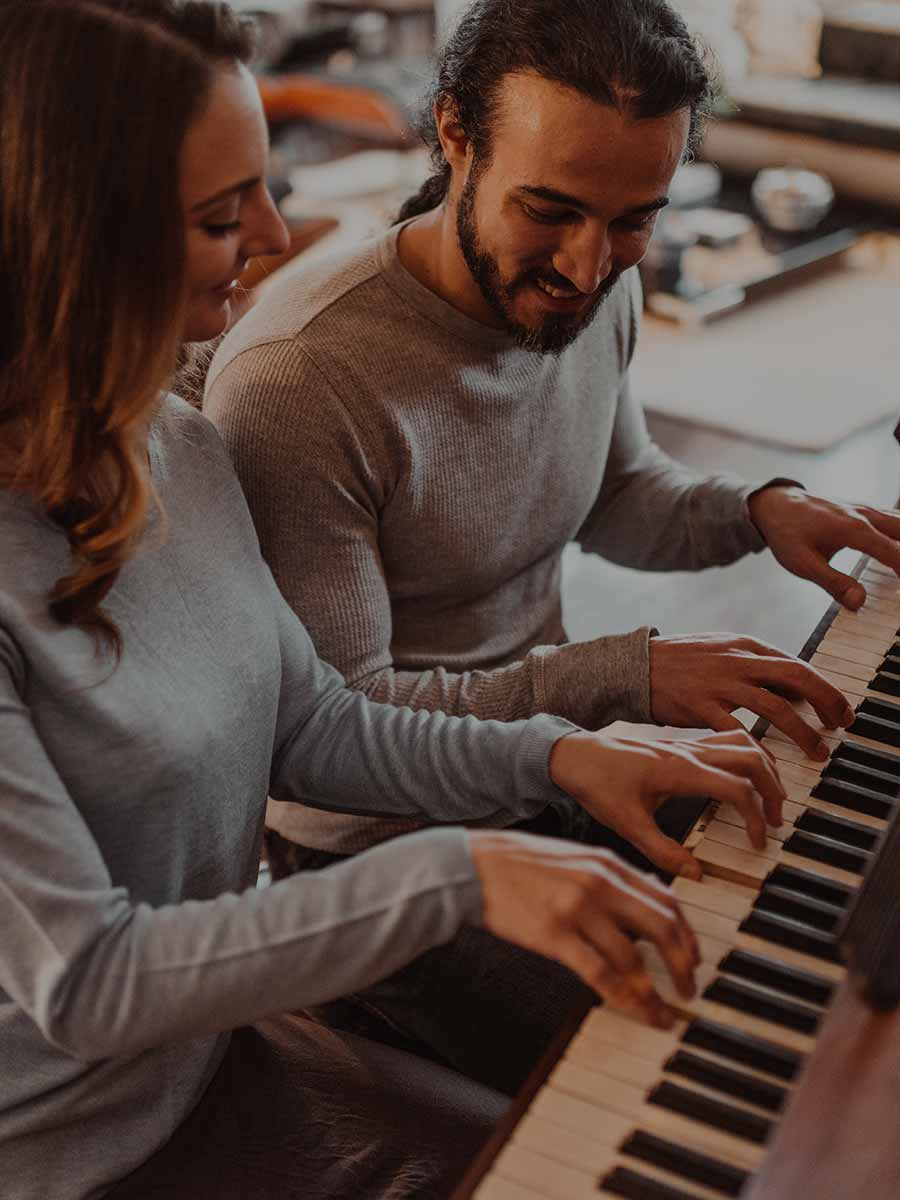 Couple learning to play the piano in a group format