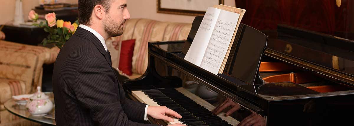 man-reading-music-on-piano