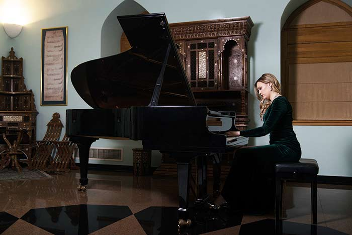 woman playing on the grand piano feat