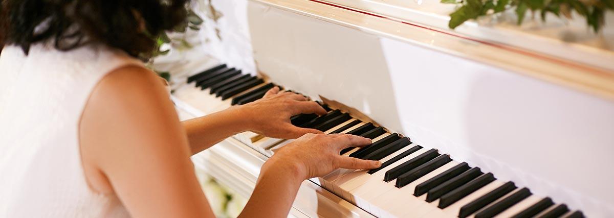 woman practising on white piano