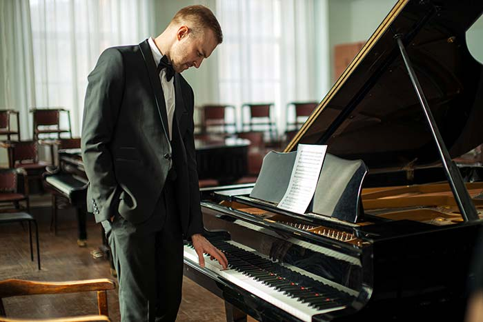 man standing in front of the piano feat