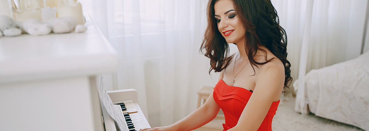 woman in red dress playing the piano