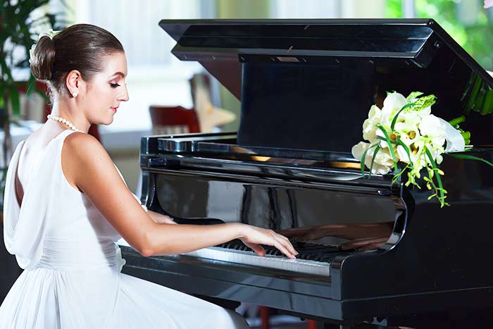 woman in white playing the piano feat