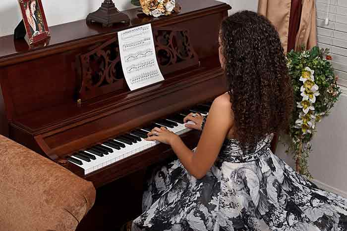 woman playing the piano at home feat