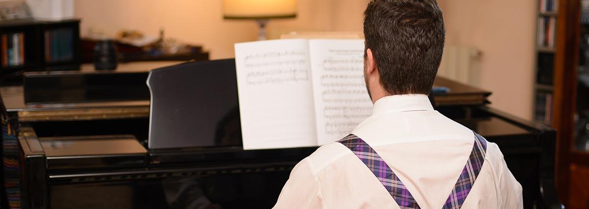 man practising piano at home